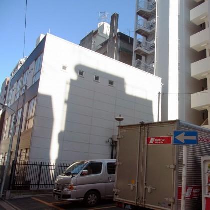 パーキングの隣に3階建てのプレハブみたいな建物があります